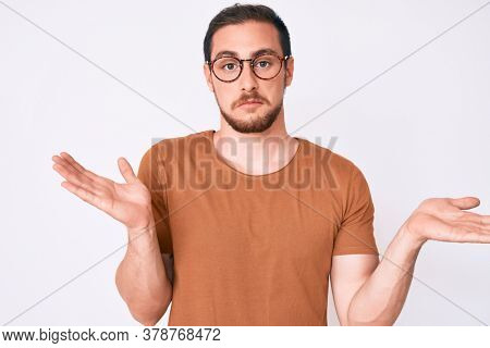 Young handsome man wearing casual clothes and glasses clueless and confused expression with arms and hands raised. doubt concept.