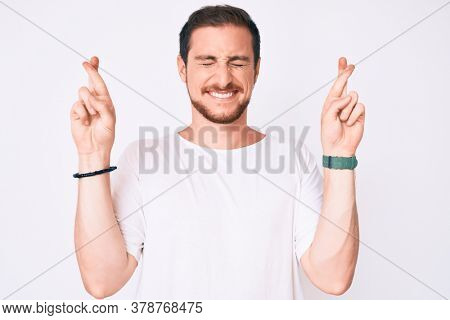 Young handsome man wearing casual white tshirt gesturing finger crossed smiling with hope and eyes closed. luck and superstitious concept.
