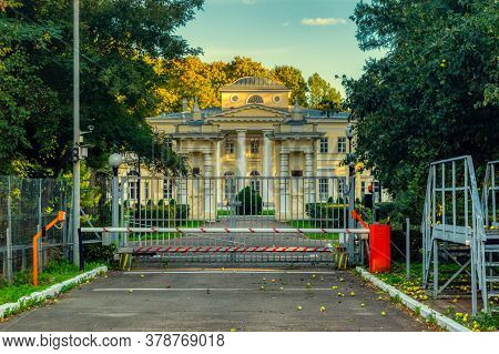An Old Mansion Surrounded By Green Trees Surrounded By A Metal Fence And The Road Is Blocked By A Ba