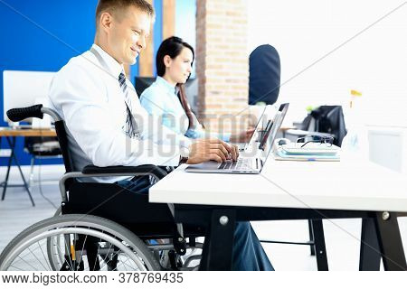 Businessman In A Wheelchair With Colleague In Office At Working Table. Equal Rights For People With