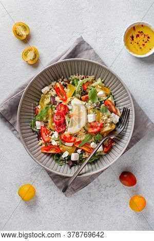 Salad With Bulgur, Cherry Tomatoes, Feta Cheese And Green Herbs On Concrete Table Top. Middle Easter