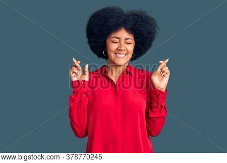 Young african american girl wearing casual clothes gesturing finger crossed smiling with hope and eyes closed. luck and superstitious concept.