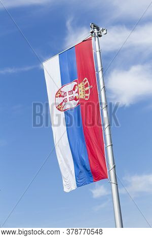 Flag Of Serbia Waving In The Wind Against White Cloudy Blue Sky