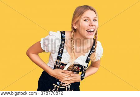 Young beautiful blonde woman wearing oktoberfest dress smiling and laughing hard out loud because funny crazy joke with hands on body.