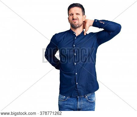Young handsome man wearing casual shirt suffering of neck ache injury, touching neck with hand, muscular pain