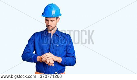 Young handsome man wearing worker uniform and hardhat in hurry pointing to watch time, impatience, upset and angry for deadline delay