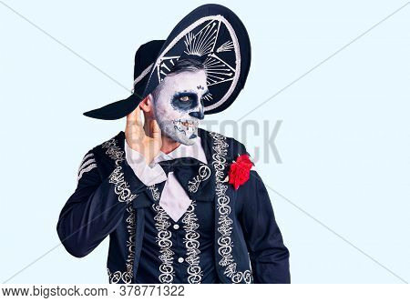 Young man wearing day of the dead costume over background smiling with hand over ear listening an hearing to rumor or gossip. deafness concept.