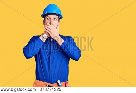 Young handsome man wearing worker uniform and hardhat feeling unwell and coughing as symptom for cold or bronchitis. health care concept.