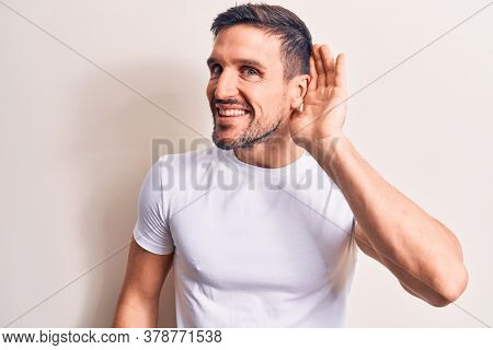 Young handsome man wearing casual t-shirt standing over isolated white background smiling with hand over ear listening and hearing to rumor or gossip. Deafness concept.