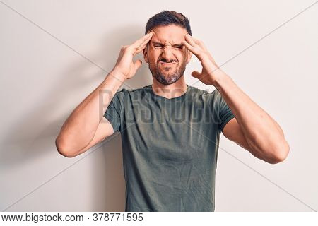 Young handsome man wearing casual t-shirt standing over isolated white background with hand on head, headache because stress. Suffering migraine.