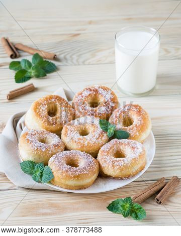 Homemade Ring-shaped Sugared Donuts On A White Plate On A Light Wooden Background, Rustic Style