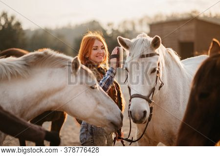 Young Joyful Cowgirl Runs With Horses On A Ranch. Close-up.