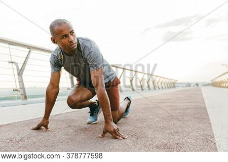 Young african man jogger exercising outdoors on a bridge