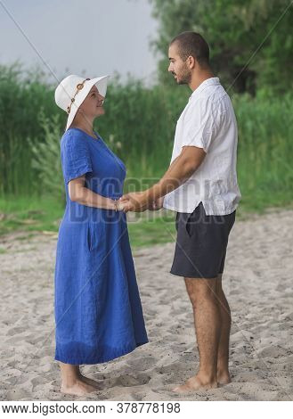 Barefoot Husband And Wife Hold Hands By The River
