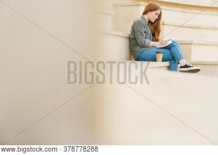 Attractive young girl writting in a notebook, drinking takeaway coffee on stairs outdoors