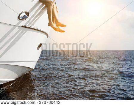 Side of luxury yacht with couple legs sunbathing in sunshine