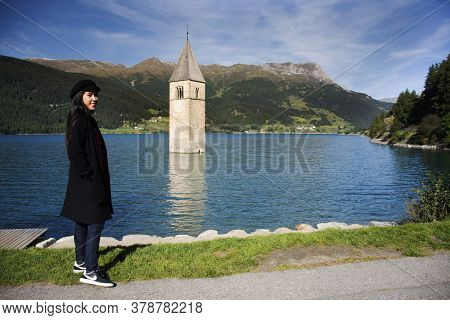 Traveler Thai Woman Travel And Posing Take Photo At Submerged Tower Of Reschensee Church Deep In Res