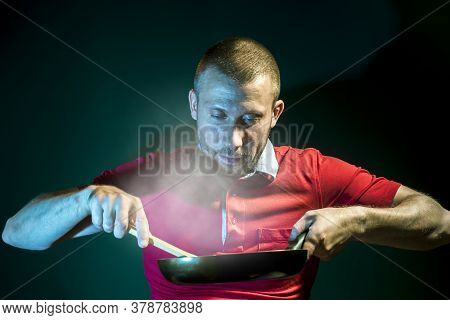 A Smiling Male Cook Cooks In A Frying Pan On A Dark Green Background