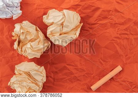 On Red Crumpled Paper Lies Heavily Crumpled Colored And Squeaky Paper, As Well As One Orange Chalk