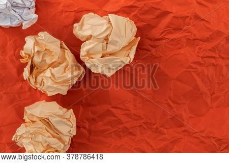 On A Crumpled Sheet Of Red Paper Lies Heavily Crumpled Orange And White Paper