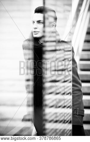 LGBTQ community lifestyle concept. Young homosexual man stands behind glass. Handsome fashionable gay male model poses outdoors. Wears red coat, gloves, and black scarf. Black and white monochrome.