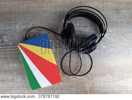 Headphones And Book. The Book Has A Cover In The Form Of Seychelles Flag. Concept Audiobooks. Learni