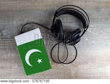 Headphones And Book. The Book Has A Cover In The Form Of Pakistan Flag. Concept Audiobooks. Learning