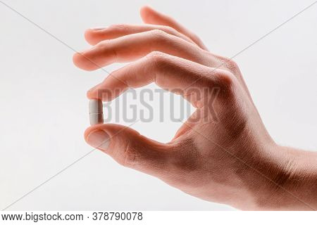 Hand Holding A Caplet Pill On White Background