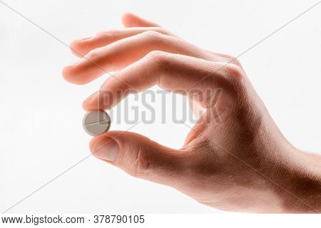 Tablet Pill In A Male Hand On White Background