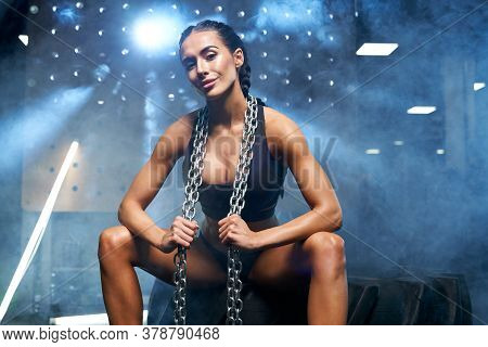 Young Smiling Fitness Woman In Black Sportswear With Braids Holding Chains On Neck. Front View Of At