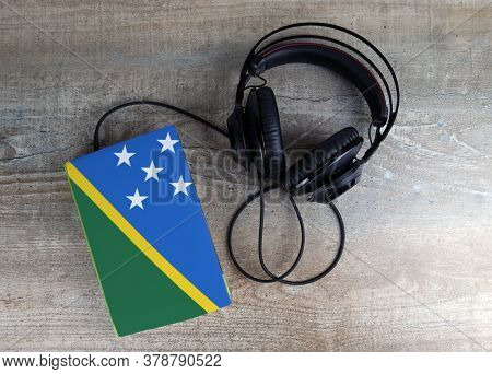 Headphones And Book. The Book Has A Cover In The Form Of Solomon Islands Flag. Concept Audiobooks. L
