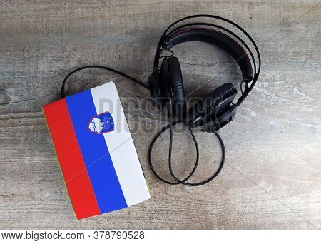 Headphones And Book. The Book Has A Cover In The Form Of Slovenia Flag. Concept Audiobooks. Learning