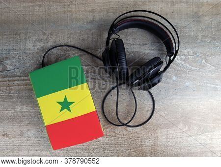 Headphones And Book. The Book Has A Cover In The Form Of Senegal Flag. Concept Audiobooks. Learning