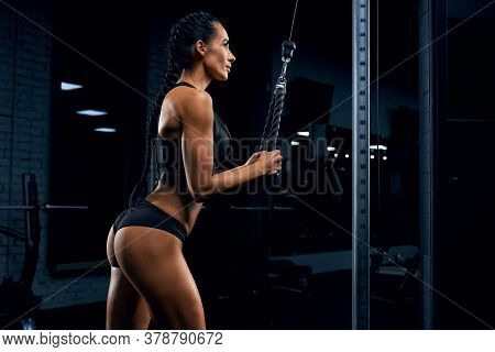 Side View Of Strong Fitness Woman In Black Sportswear With Long Braids Training Triceps. Attractive