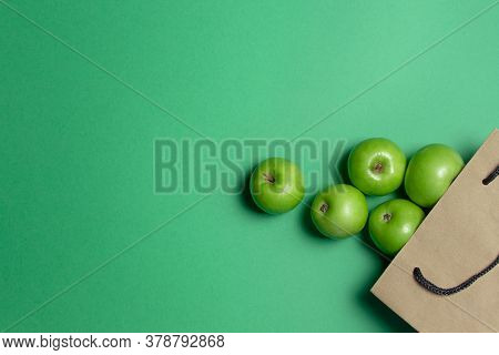 Green Apples On A Green Background. The Apples Fell Out Of The Paper Bag. Photo From Above. There Is