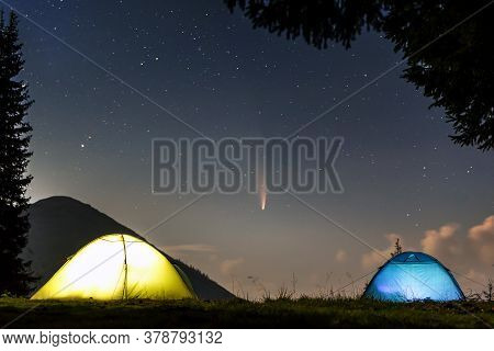 Two Brightly Lit Tourist Tents On Forest Clearing In Mountains With Starry Sky And C/2020 F3 (neowis