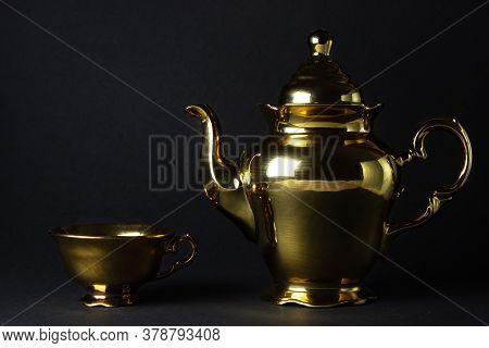 Gold Tea Set On A Black Background. The Teapot And Teacup Are Next To Each Other.