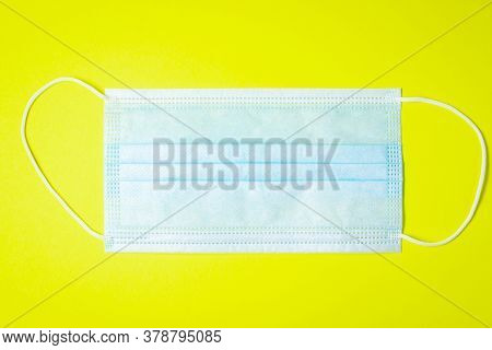 Medical Mask On A Yellow Background. Quarantine. Protective Agent. Medicine Concept