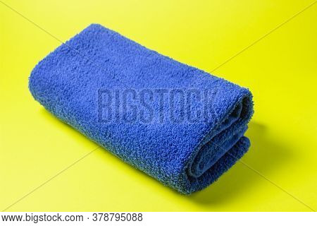 Blue Towel On A Yellow Background. A Long Awaited Vacation. A Trip To The Sea.