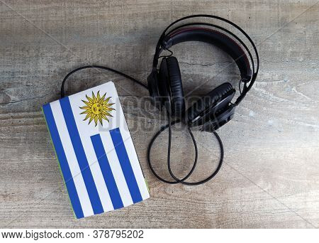 Headphones And Book. The Book Has A Cover In The Form Of Uruguay Flag. Concept Audiobooks. Learning