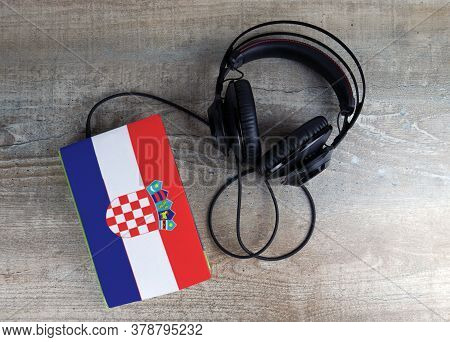 Headphones And Book. The Book Has A Cover In The Form Of Croatia Flag. Concept Audiobooks. Learning