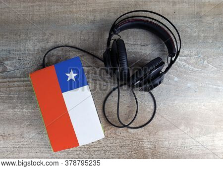 Headphones And Book. The Book Has A Cover In The Form Of Chile Flag. Concept Audiobooks. Learning La