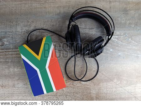 Headphones And Book. The Book Has A Cover In The Form Of South Africa Flag. Concept Audiobooks. Lear