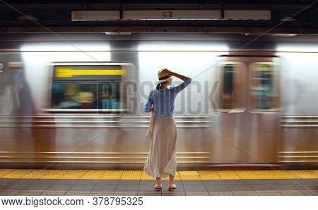 Attractive girl waiting for a train in the subway. USA, NYC 2019