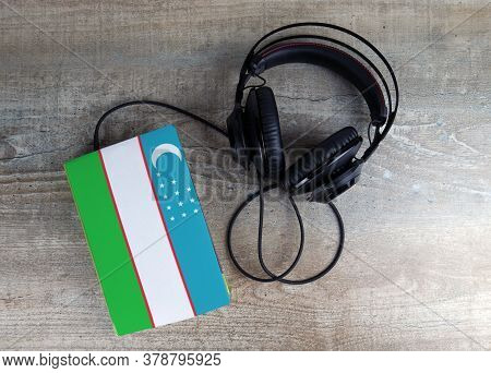 Headphones And Book. The Book Has A Cover In The Form Of Uzbekistan Flag. Concept Audiobooks. Learni