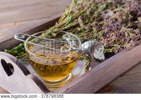Herbal Treatment. Tea With Oregano And A Bunch Of Herbs In A Wooden Tray On The Table
