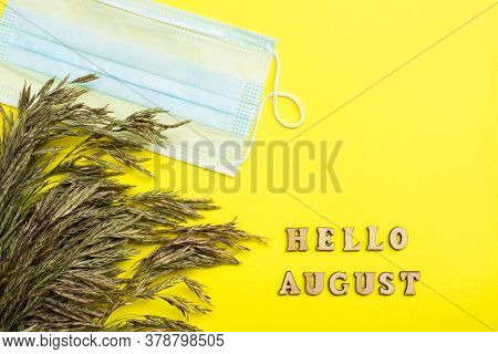 Hello August. Life In Quarantine. Text In Wooden Letters, Ears Of Grass And A Protective Mask On A Y