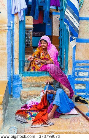 Indian traditional family. Women sewing clothes. shoot was made in Jaisalmer' street Feb.2013. Rajastan, India