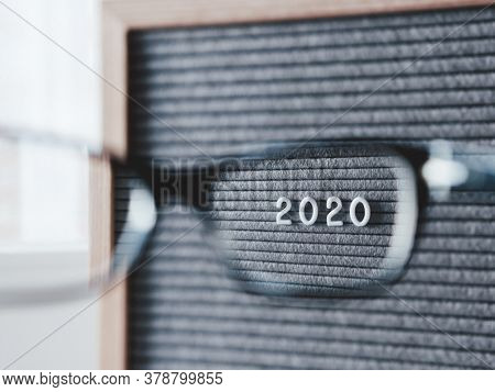 Top View On Letterboard With Numbers 2020 Through Eyeglasses. Flat Lay Concept Of 2020 Year Results.