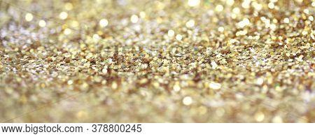 Gold (bronze) glitter shine dots confetti. Abstract light blur blink sparkle defocus horizontal backgound.